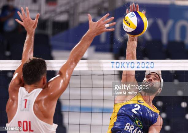Bruno Oscar Schmidt competes against Michal Bryl of Team Poland during the Men's Preliminary - Pool E beach volleyball on day seven of the Tokyo 2020...
