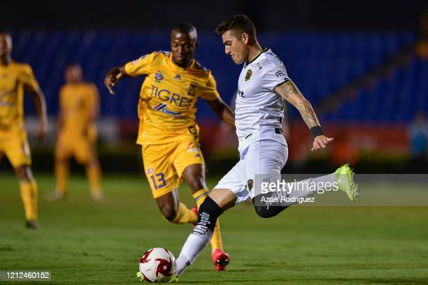 Bruno Romo of Juárez kicks the ball while observed by Enner Valencia of Tigres during the 10th round match between Tigres UANL and FC Juarez as part...
