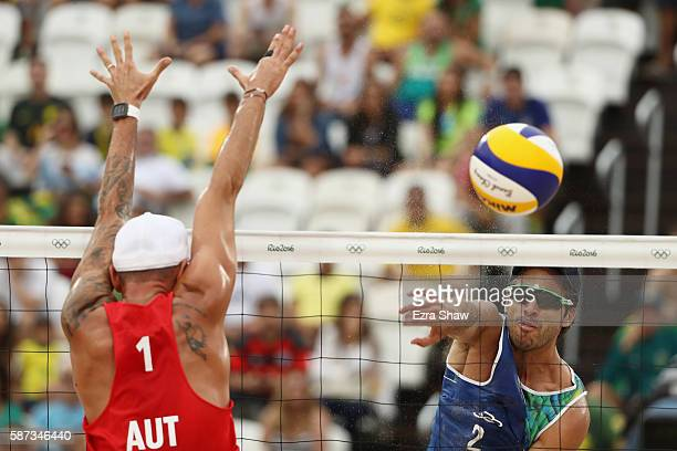 Bruno Schmidt Oscar of Brazil hits as Clemens Doppler of Austria attempts to block during the Men's Beach Volleyball preliminary round Pool A match...