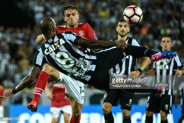 TOPSHOT Bruno Silva of Brazil's Botafogo kicks a ball in front of Facundo Sanchez of Argentinas Estudiantes de La Plata during their Copa...
