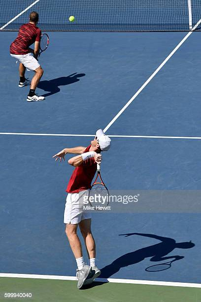 Bruno Soares of Brazil and Jamie Murray of Great Britain serve to Chris Guccione of Australia and Andre Sa of Brazil during their Men's Doubles...