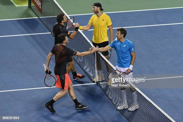 Bruno Soares of Brazil and Jamie Murray of Great Britain shake hands with Dominic Inglot of Great Britain and Daniel Nestor of Canada after their...