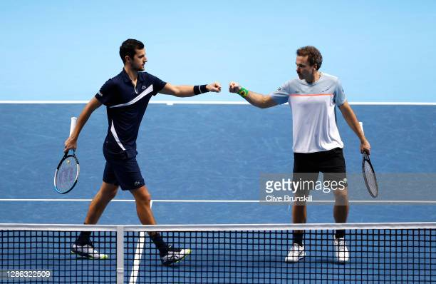 Bruno Soares of Brazil and partner Mate Pavic of Croatia bumps fists during their doubles match against Marcel Granollers of Spain and Horacio...