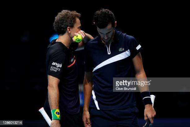 Bruno Soares of Brazil talks tactics with partner Mate Pavic of Croatia during their doubles match against Jurgen Melzer of Austria and Edouard...