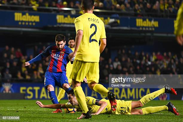 Bruno Soriano of Villarreal CF blocks the ball with his hand as Lionel Messi of FC Barcelona shoots towards goal during the La Liga match between...