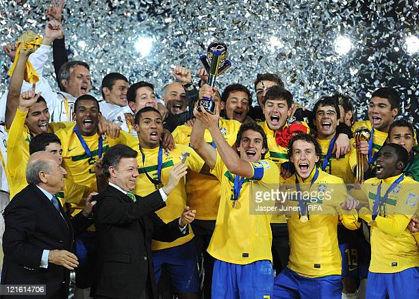 Bruno Uvini of Brazil holds the trophy aloft amid his teammates and FIFA President Joseph Sepp Blatter and Colombian President Juan Manuel Santos...