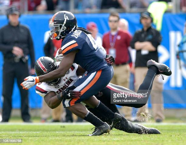 J Brunson of the South Carolina Gamecocks tackles Olamide Zaccheaus of the Virginia Cavaliers during the first half of the Belk Bowl at Bank of...