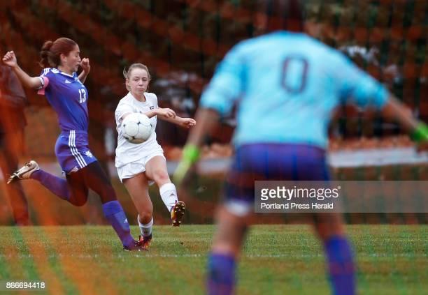 Brunswick's Marley Groat takes a shot on Lewiston goalkeeper Gemma Landry while defen der Taylor Chamberlain tries to block