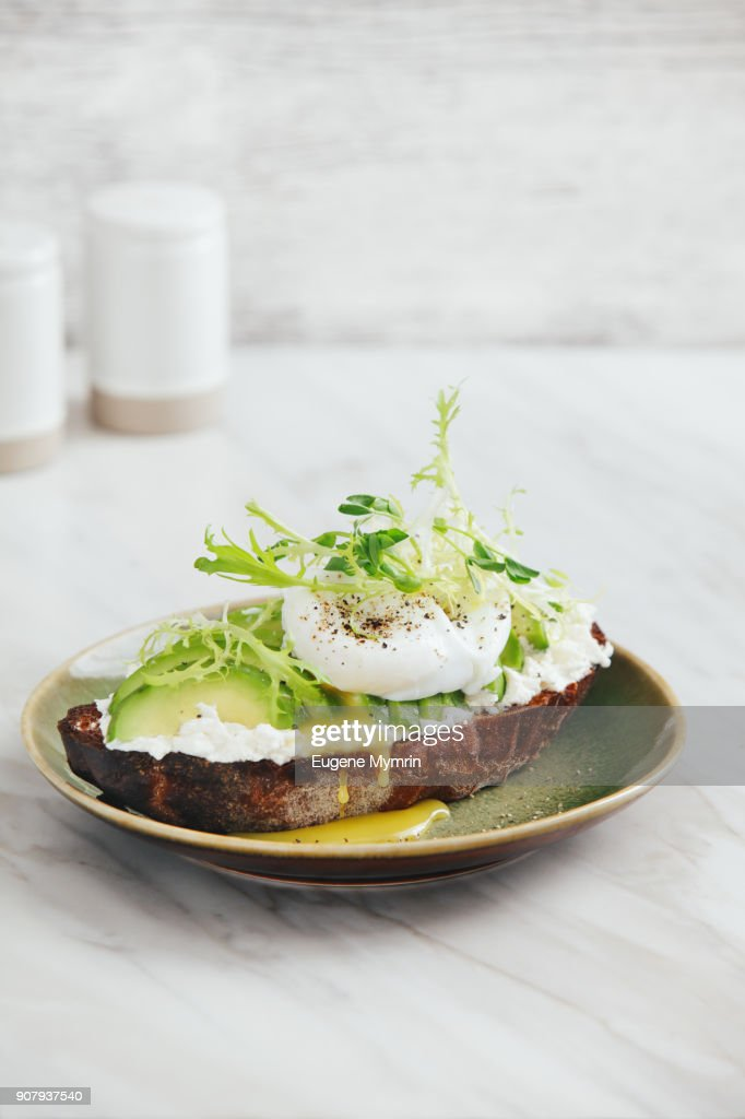 Bruschetta with avocado, ricotta and poached egg : Stock-Foto