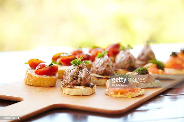 bruschetta with cheese, tomatoes, foie gras, and wild salmon - foie gras stock photos and pictures