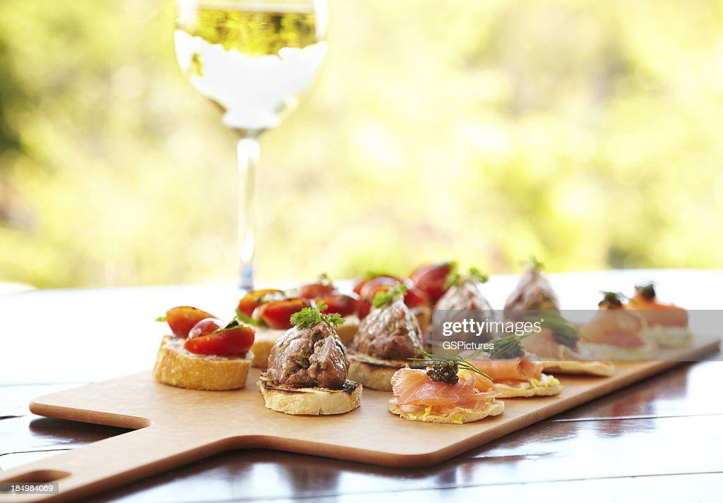 Bruschetta with cheese, tomatoes, foie gras, and wild salmon : Stock Photo