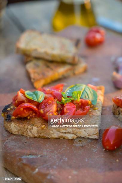 bruschetta with fresh tomato and basil on a chopping board - image stock pictures, royalty-free photos & images