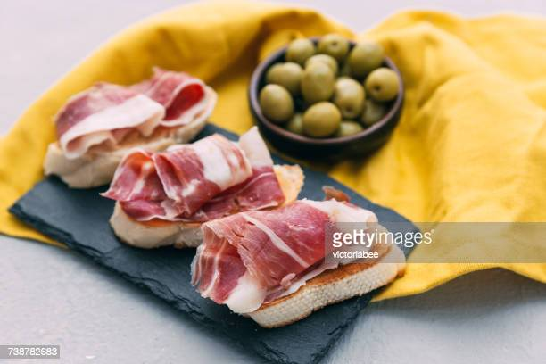 bruschetta with prosciutto and a bowl of olives - serrano ham stock photos and pictures
