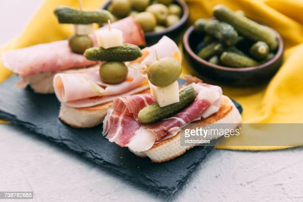 Bruschetta with prosciutto, olives, cheese and gherkins