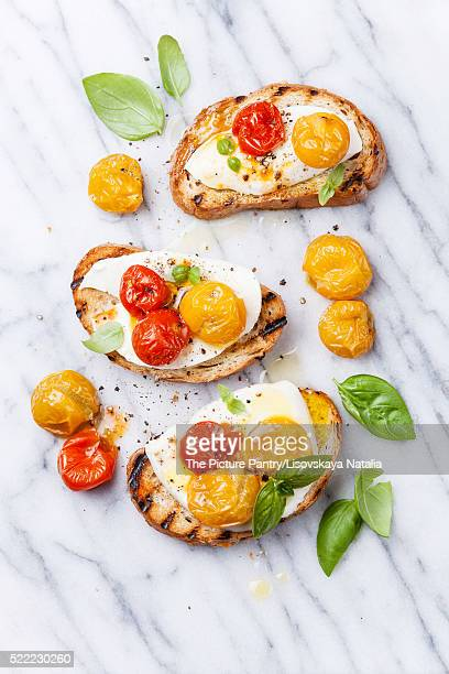 Bruschetta with roasted tomatoes and mozzarella cheese on grille