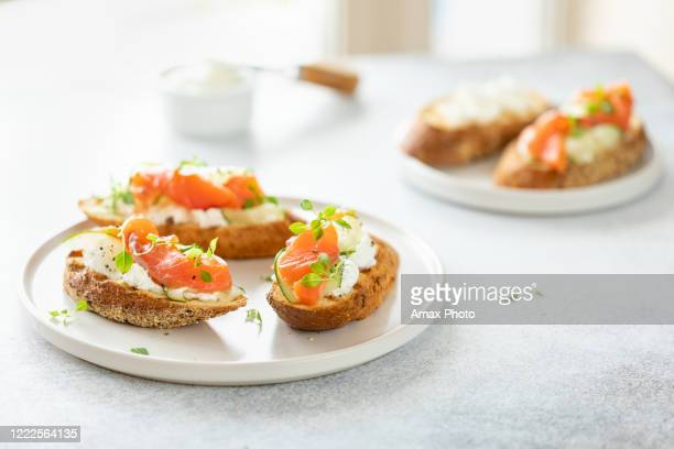 bruschetta with salmon, curd cheese and cucumber on toast in high key style on white background. - appetizer stock pictures, royalty-free photos & images