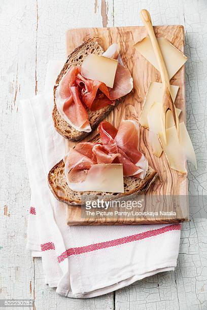 Bruschettas with cheese and ham on bread on blue wooden backgrou