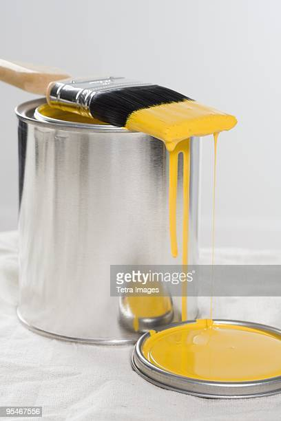 Brush and can of yellow paint