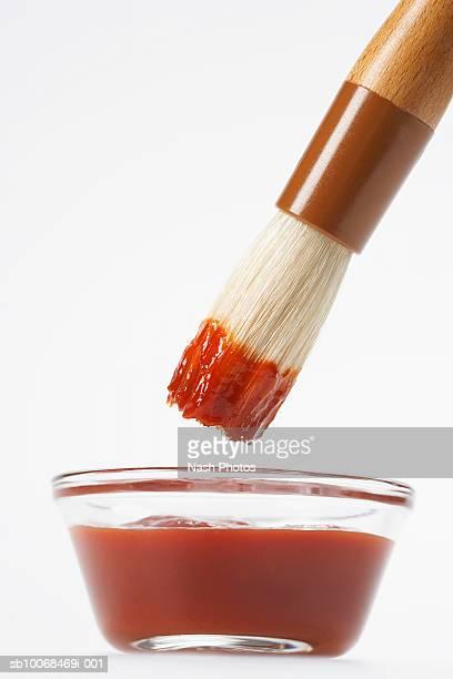 brush dipping into bbq sauce - barbeque sauce fotografías e imágenes de stock