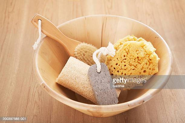 brush, seasponge, loofah and foot pumice in wooden bath bowl, - loofah stock photos and pictures
