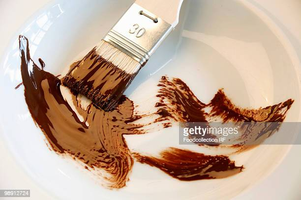 brush with chocolate in bowl, close-up - basting brush stock photos and pictures