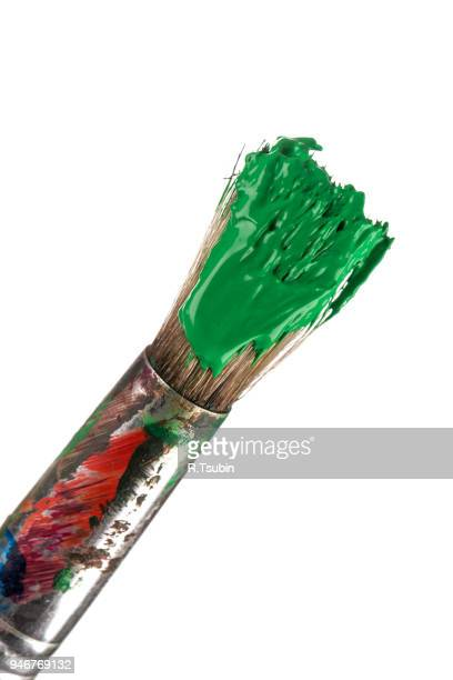 Brush with green paint isolated on white background
