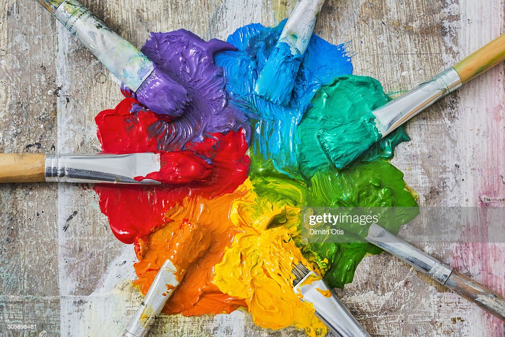 Brushes and oil paint, messy spectrum of colours : Stock Photo