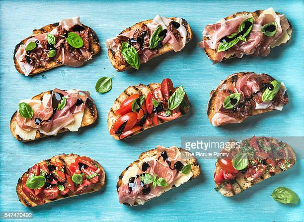 Brushetta snacks for wine. Variety of small sandwiches on blue-painted wooden backdrop