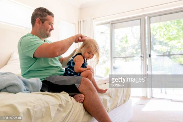 brushing daughters hair - child in bed clothed stock pictures, royalty-free photos & images