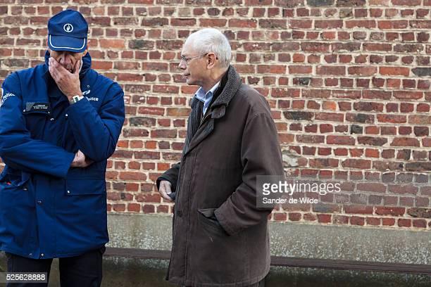 Brussels 2012 14 october. Mr van Rompuy in front of a brick wall in his hometown saint genesius rode, talking to the police