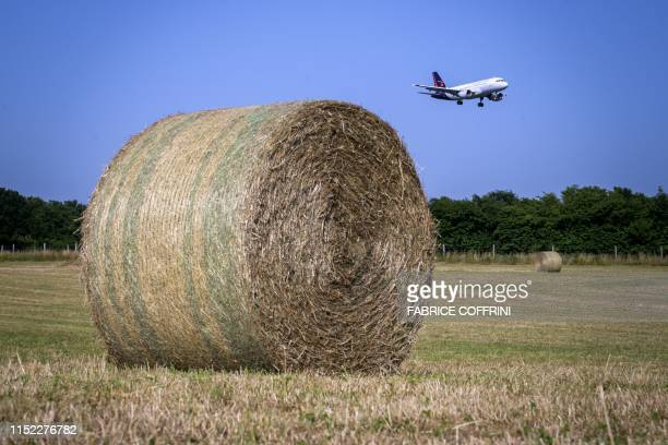 A Brussels Airlines commercial plane is landing above a field with large round straw bales next to Geneva Airport on June 26 2019 in Geneva