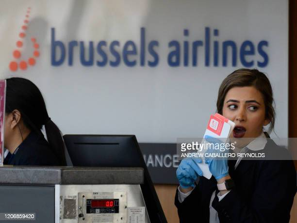 A Brussels Airlines employee wearing gloves as a precaution against COVID19 speaks with a coworker at checkin area at Dulles International airport in...