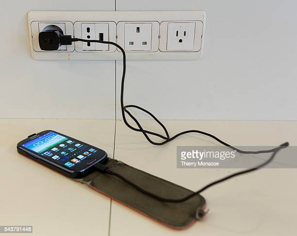 Brussels Airport Belgium December 22 2015 A smartphone is recharge on a AC International power plugs
