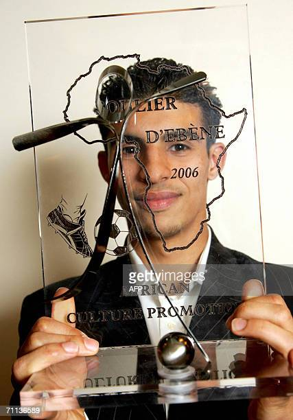 A file photo taken 24 April 2006 shows Dutch player Mbark Boussoufa of AA Gent posing with his trophy after winning the Ebony Shoe award for Best...