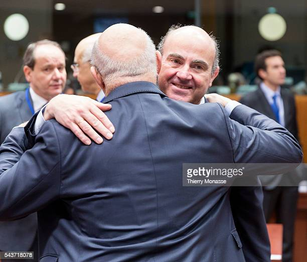 Brussels Belgium February 17 2015 French Finance Public Accounts Minister Michel Sapin hugg the Spanish Minister of Economy Competitiveness Luis De...