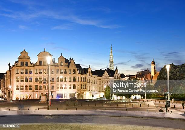 Brussels cityscape with majestic City Hall bell tower in Gothic style and medieval houses illuminated at dusk in Brussels, Belgium
