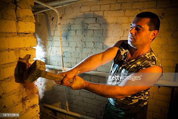 brutal construction worker destroying brick wall with sledgehammer - demolishing stock pictures, royalty-free photos & images