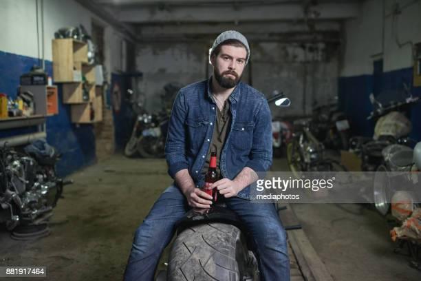 brutal gut aussehend kfz-mechaniker in garage - feierabend stock-fotos und bilder