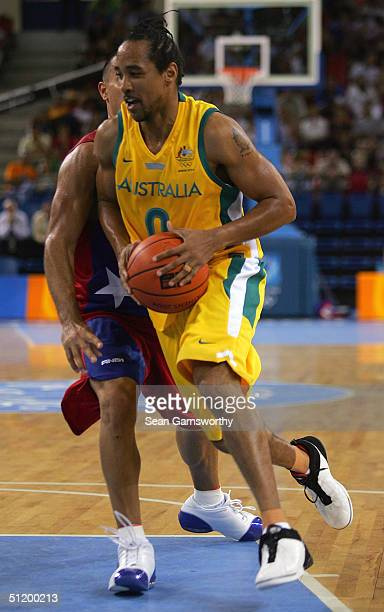 Bruton for Australia drives past Carlos Arroyo of Puerto Rico in a men's basketball preliminary game August 21, 2004 during the Athens 2004 Summer...