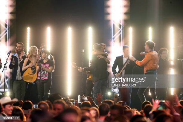 Bryan Adams and Sarah McLachlan hug after performing Adams' song 'Summer of 69' with several musicians during the JUNO awards show finale at the...