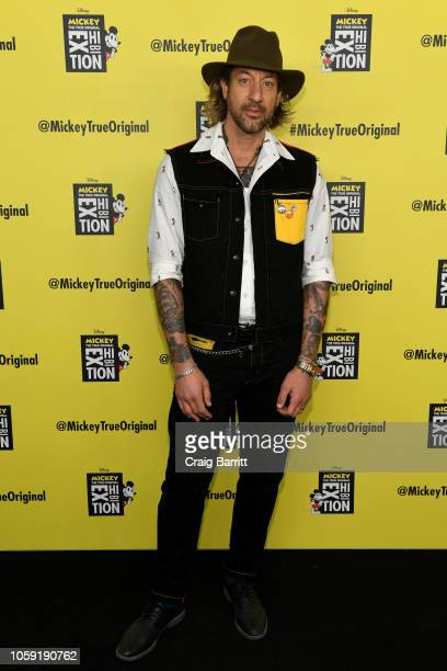 Bryan Anderson wearing rag and bone x Disney Mickey Mouse attends Mickey The True Original Exhibition reception to commemorate Mickey Mouse's 90th...