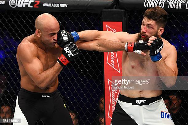 Bryan Barberena punches Warlley Alves of Brazil in their middleweight bout during the UFC 198 event at Arena da Baixada stadium on May 14, 2016 in...