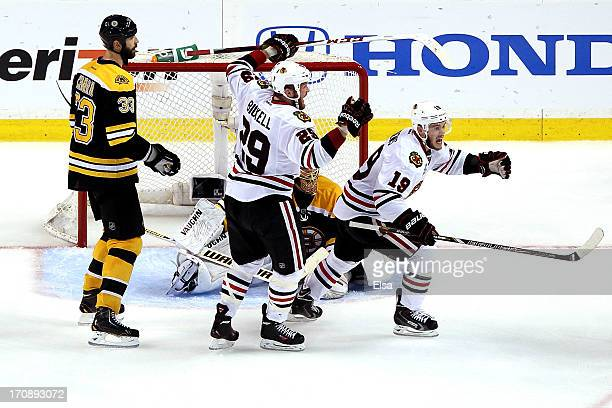 Bryan Bickell and Jonathan Toews of the Chicago Blackhawks celebrate after Brent Seabrook scores the game winning goal against Tuukka Rask of the...