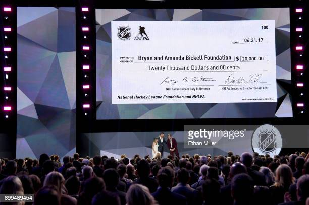 Bryan Bickell and wife Amanda Bickell speak onstage as an image of a $20000 check is displayed to the Bickell's foundation during the 2017 NHL Awards...