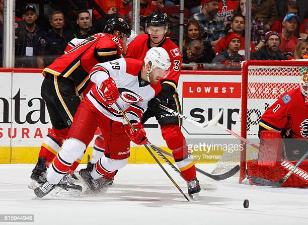 Bryan Bickell of the Carolina Hurricanes battles for the puck against Dougie Hamilton of the Calgary Flames at Scotiabank Saddledome on October 20...
