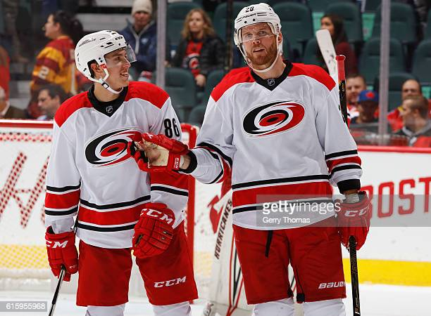 Bryan Bickell of the Carolina Hurricanes chats with teammate Teuvo Teravainen during against the Calgary Flames at Scotiabank Saddledome on October...