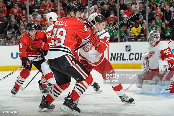 Bryan Bickell of the Chicago Blackhawks and Cory Emmerton of the Detroit Red Wings watch for the puck during the NHL game on March 16 2014 at the...