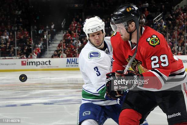 Bryan Bickell of the Chicago Blackhawks and Kevin Bieksa of the Vancouver Canucks chase after the puck in Game Six of the Western Conference...