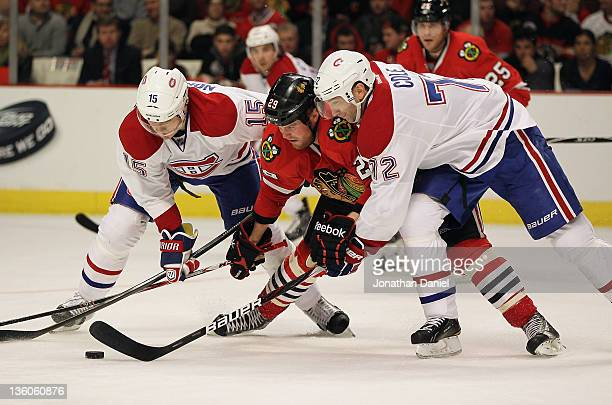 Bryan Bickell of the Chicago Blackhawks battles for the puck with Petteri Nokelainen and Erik Cole of the Montreal Canadiens at the United Center on...