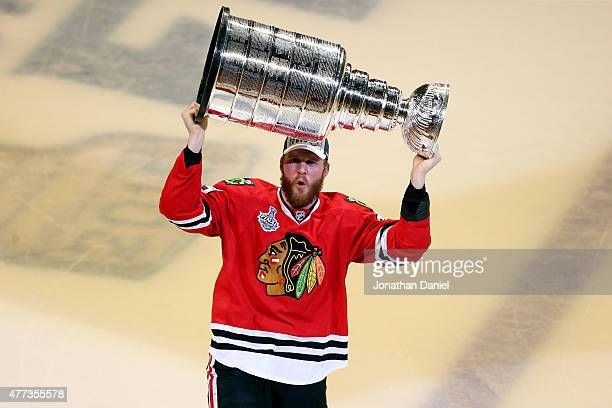 Bryan Bickell of the Chicago Blackhawks celebrates by hoisting the Stanley Cup after defeating the Tampa Bay Lightning by a score of 20 in Game Six...